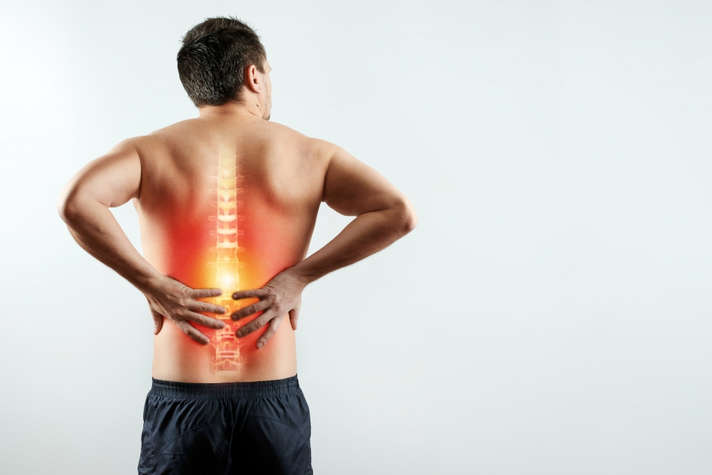 Lower back pain image of man standing holding his back.