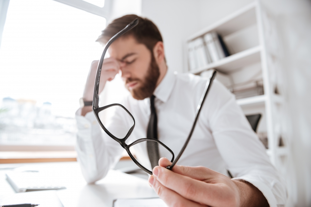 Image of young office worker with a headache.