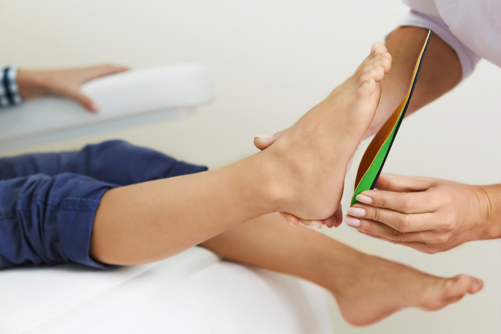 Image to show fitting of custom orthotic insoles for knee pain caused by flat feet.
